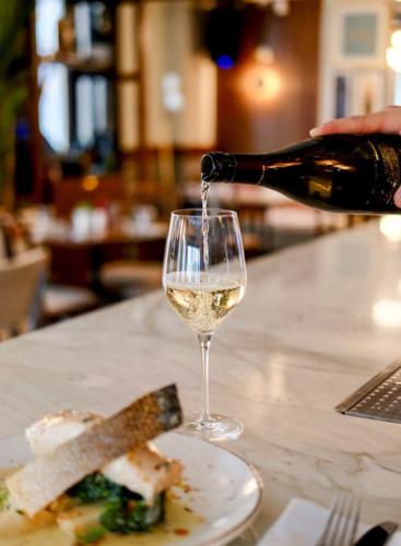 Copa de vino blanco para maridaje por afinidad con pescado